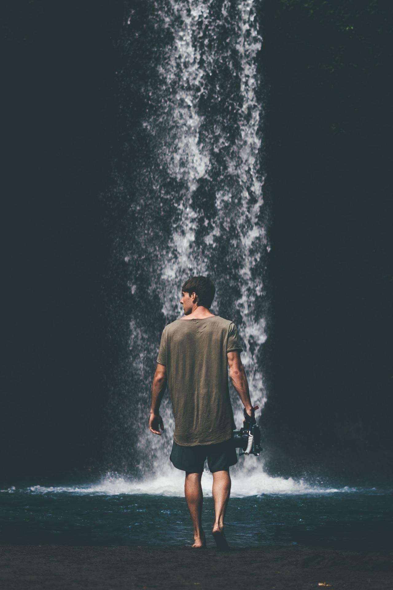 Homme de dos dans une cascade